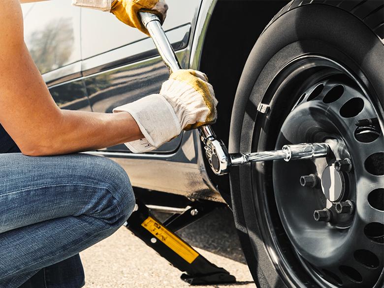 Někdo utahuje pneumatiky na autě.