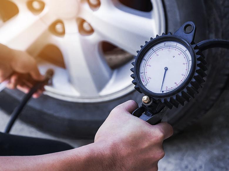 Někdo měří tlak vpneumatikách na svém autě.