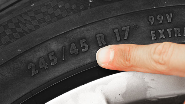 Palec wskazuje rozmiar opony na oponie samochodowej.