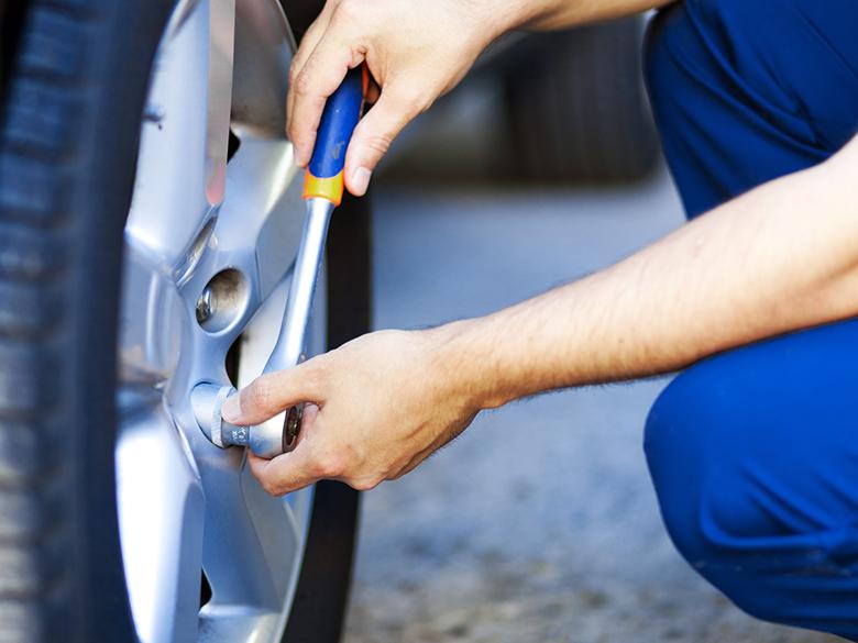 Ktoś dokręca śruby przy kołach samochodu.