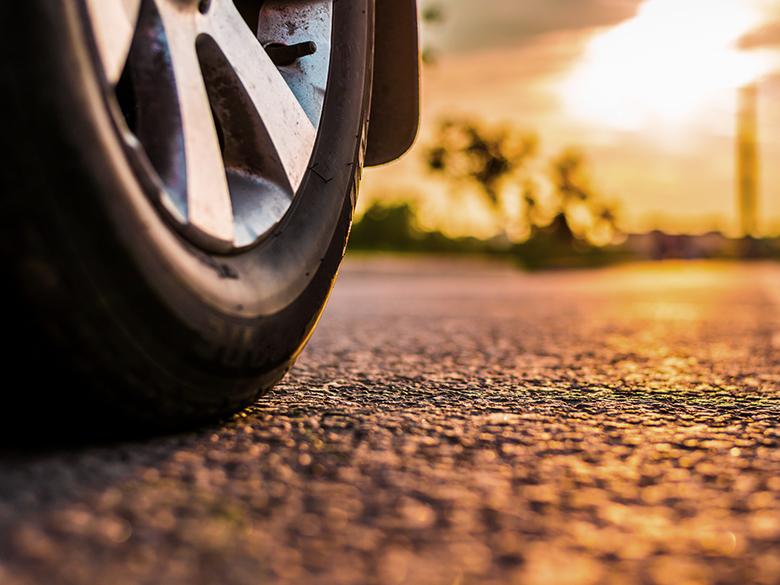 Ein Autoreifen mit der nötigen Mindestprofiltiefe steht auf einer Straße.