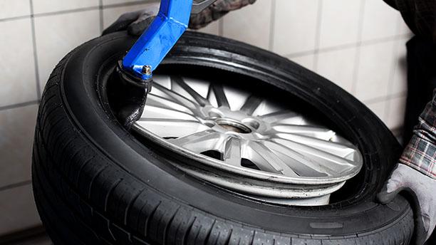 In einer Werkstatt wird ein Reifen montiert.