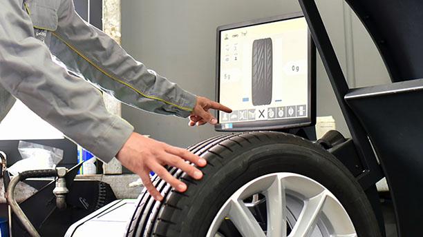 In einer Werkstatt wird ein Reifen ausgewuchtet.