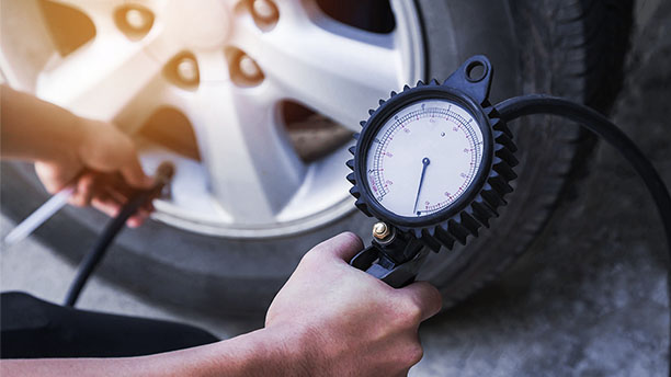 Detail osoby kontrolující tlak v pneumatice. Tlakoměr je dobře viditelný.