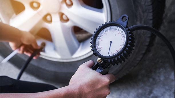 Záber zblízka na človeka pri kontrole tlaku pneumatík. Jasne vidieť tlakomer.