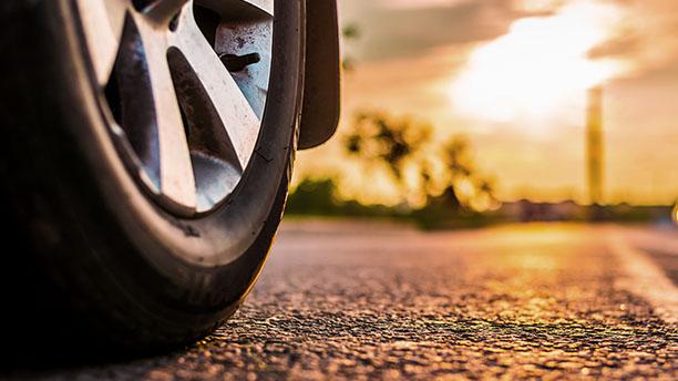 Opona samochodowa o wymaganej minimalnej głębokości bieżnika stoi na drodze.