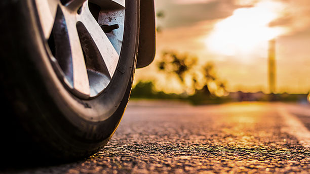 A car tyre with the required minimum tread depth stands on a road.
